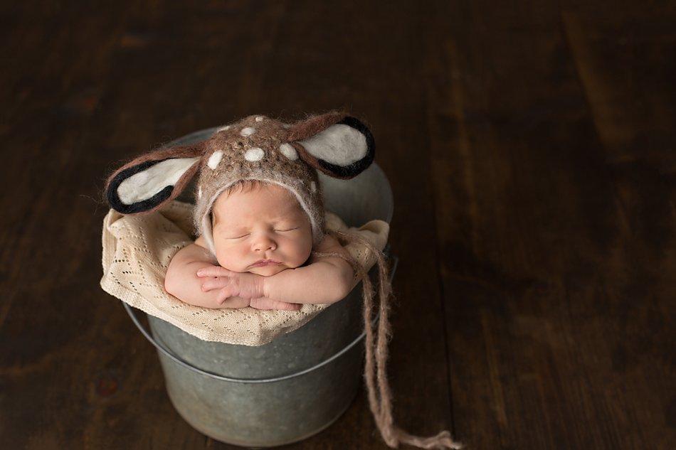 Newborn baby boy in a bucket wearing a deer bonnet.