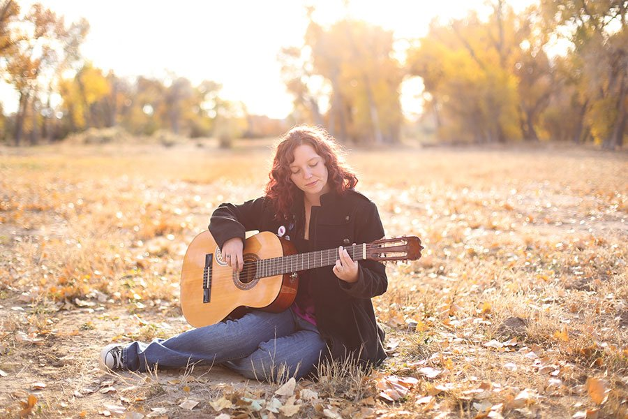 Pueblo senior McCartney playing her guitar in a field by K.D. Elise Photography