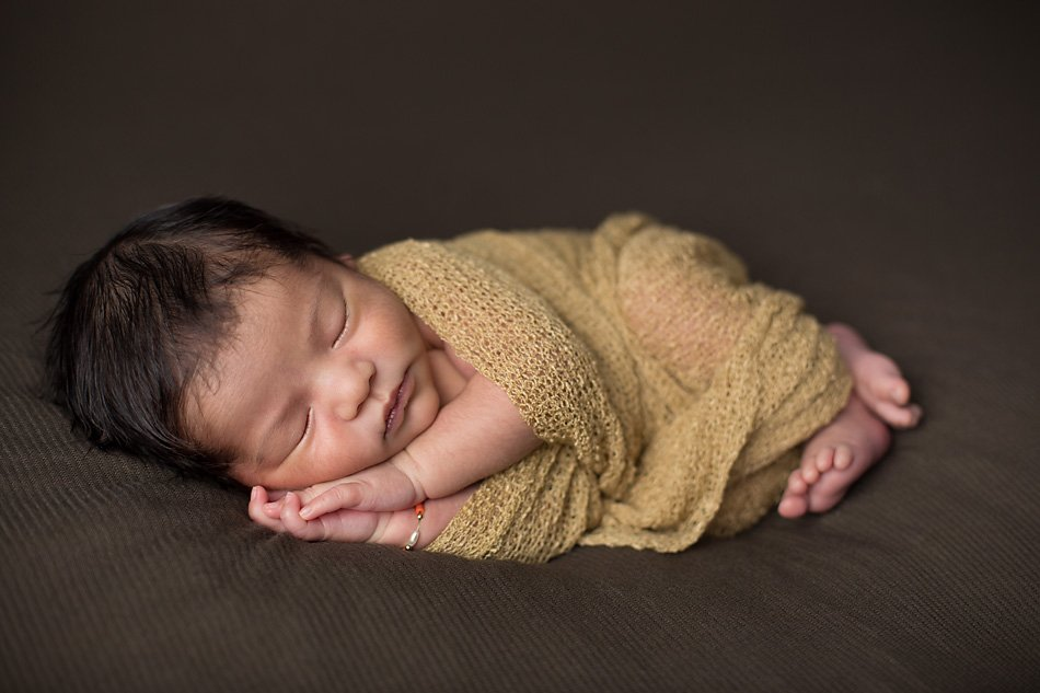 Wrapped newborn boy on ribbed fabric by Pueblo newborn photographer K.D. Elise Photography