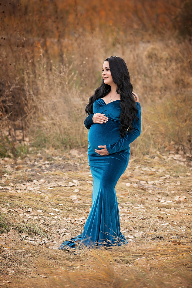 Maternity portrait of mom in blue gown standing in field. By Pueblo maternity photographer K.D. Elise Photography.