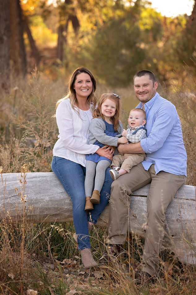 Family photo of mom and dad sitting on a fallen log with their two kids during family portraits with K.D. Elise Photography.