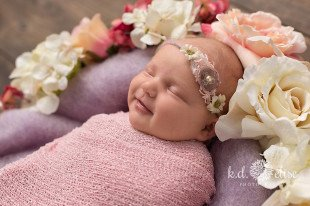 Newborn baby girl surrounded by flowers.