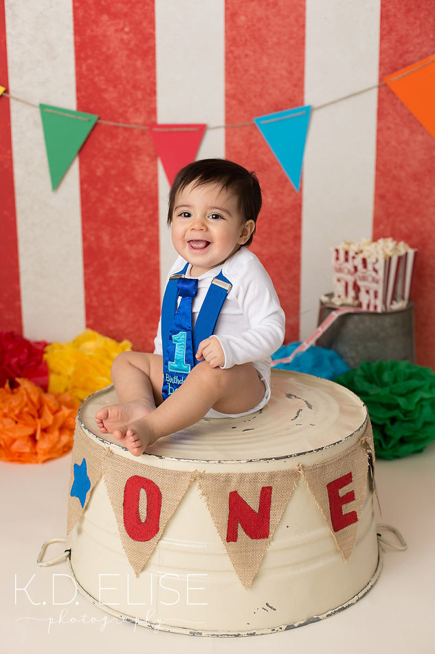 Circus themed first birthday photos of little boy sitting on ring master