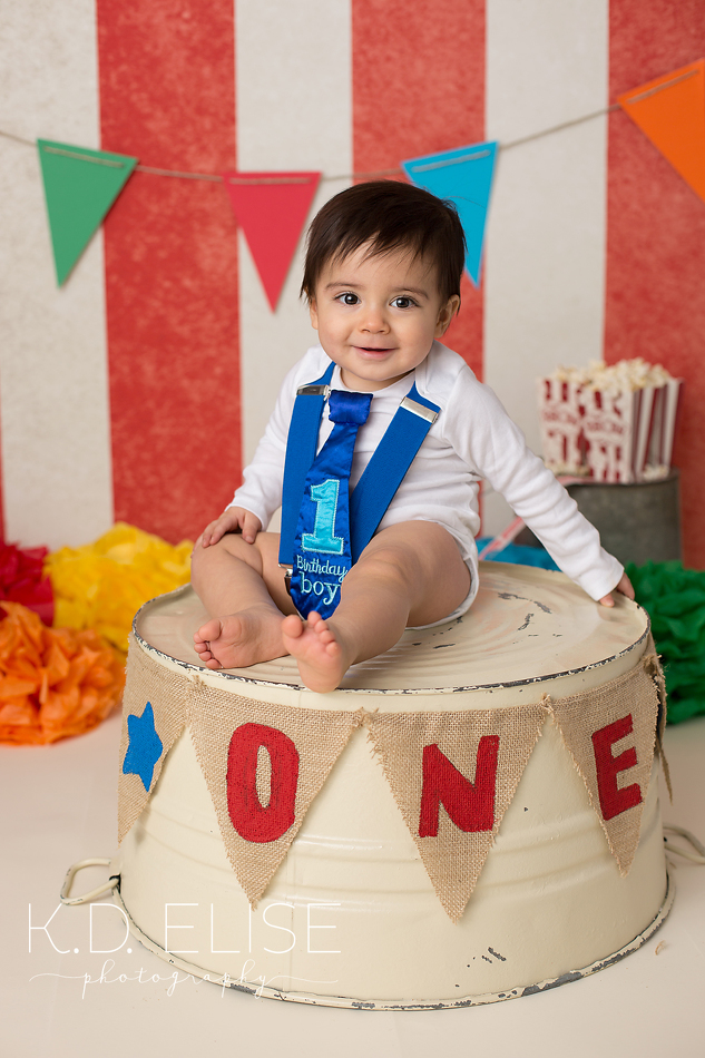 Circus themed first birthday photos of little boy in blue suspenders and tie sitting on ring master