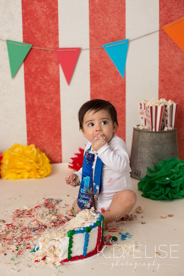 Circus themed first birthday cake smash photo of baby boy eating cake.
