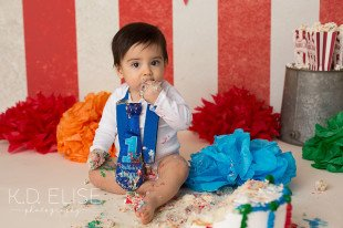 Baby boy eating birthday cake during first birthday cake smash photos by K.D. Elise Photography