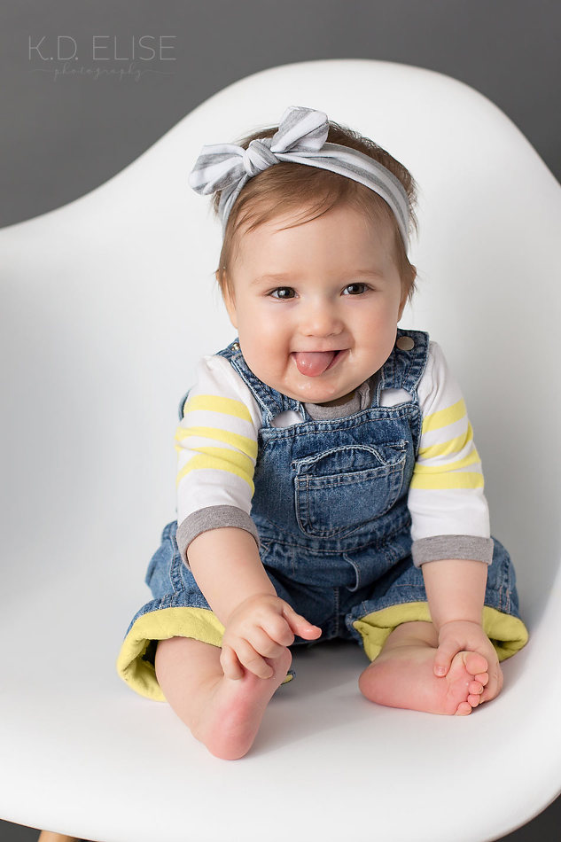 Smiling baby girl in yellow and grey striped shirt and blue overalls. Baby photography by Colorado Springs photographer K.D. Elise Photography.
