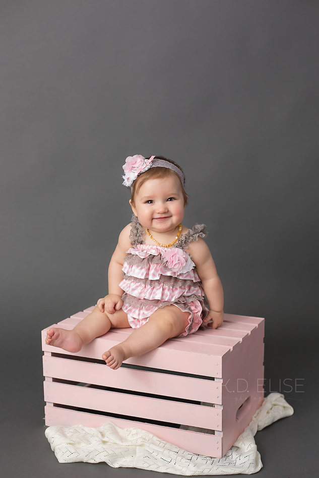 Smiling baby girl sitting on a pink crate in front of a grey backdrop. Colorado Springs baby photography by K.D. Elise Photography.