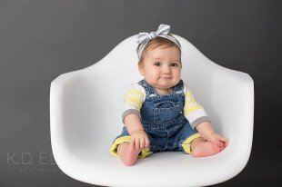 Baby girl in yellow and blue, sitting in a white chair. Colorado Springs baby photography by K.D. Elise Photography.