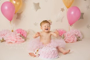 Smiling baby girl eating birthday cake during Twinkle Twinkle Little Star themed cake smash.