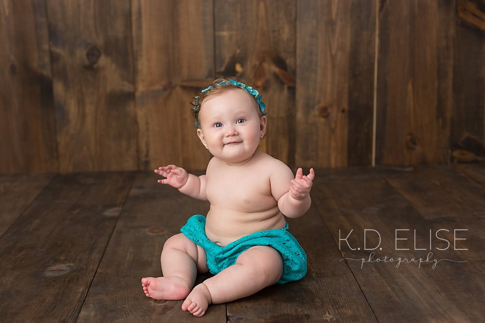 Six month old baby girl in teal diaper cover and headband sitting on a wooden backdrop smiling at the camera during her six month baby portraits with Colorado Springs baby photographer K.D. Elise Photography.