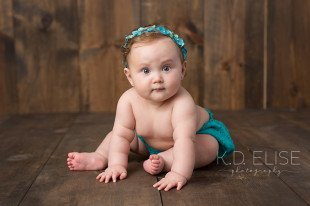 Baby girl in teal outfit sitting on a wooden backdrop. Baby portraits by Colorado Springs photographer K.D. Elise Photography.