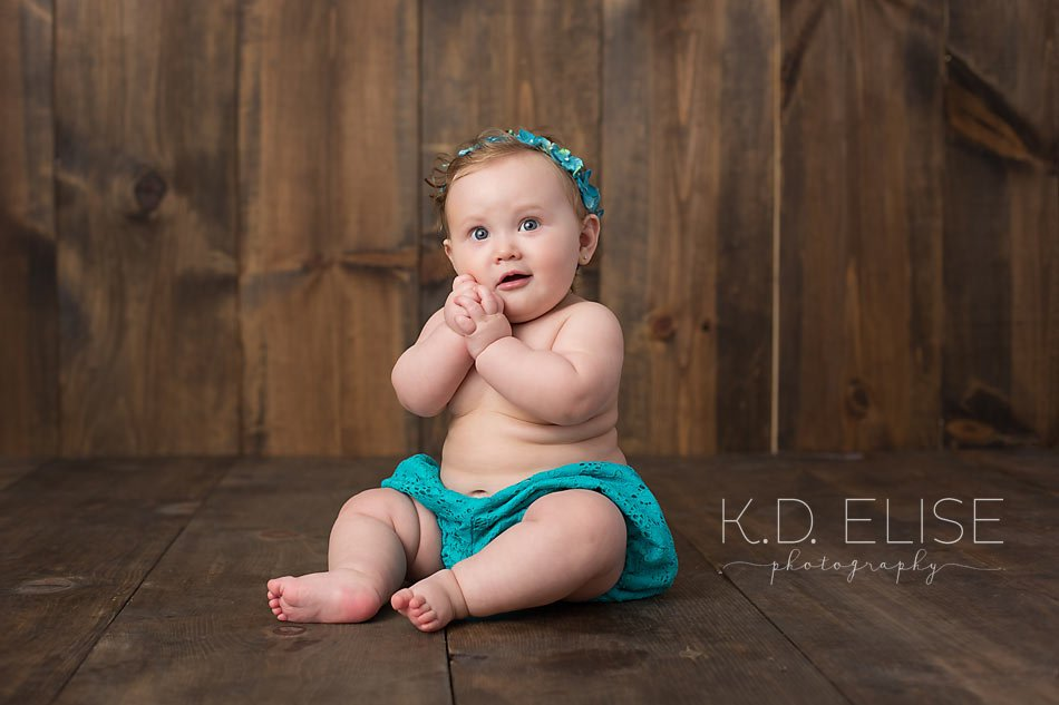 Smiling baby girl in teal outfit sitting on a wooden backdrop makes cute faces at the camera during six month baby portraits with K.D. Elise Photography.