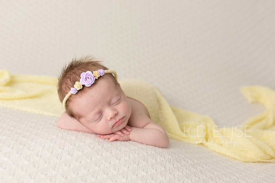 Newborn girl on cream blanket, facing the camera while wearing yellow wrap and purple and yellow headband. Newborn photography by Pueblo photographer K.D. Elise Photography.