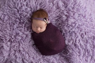 Newborn baby girl wrapped in purple and wearing a purple headband.