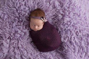 Newborn baby girl wrapped in purple and wearing a purple headband.