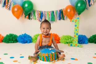 Cake smash photo of little boy with orange, blue and green setup. First birthday photos by Pueblo photographer K.D. Elise Photography.