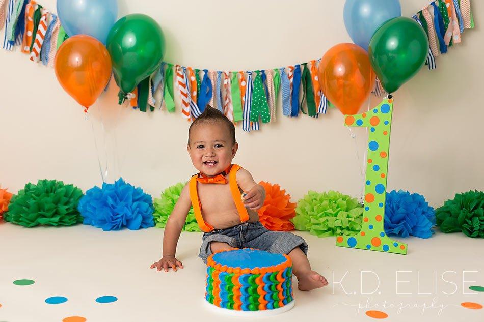 Orange, blue and green cake smash first birthday photos of little boy.