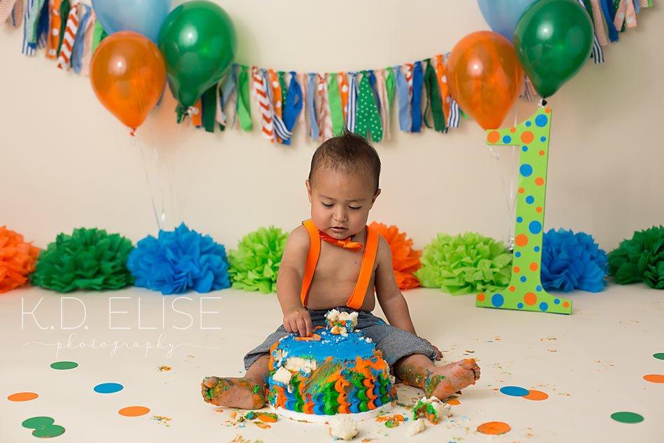 Baby boy eating cake during blue, orange and green cake smash with Pueblo photographer K.D. Elise Photography.