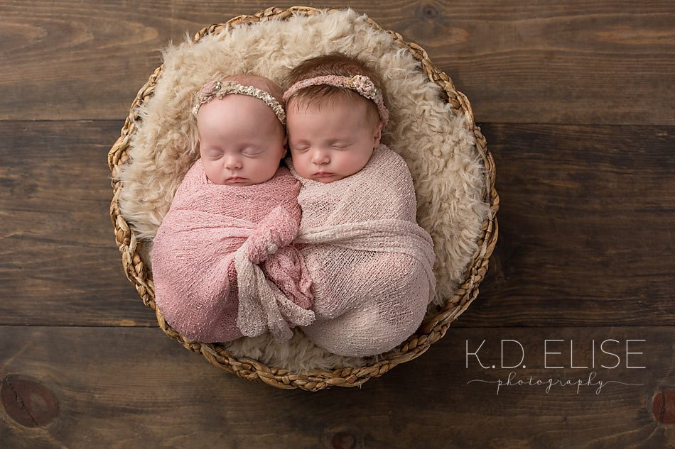 Twin newborn girls wrapped in pink resting in a basket newborn photography by k d