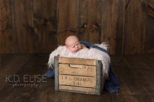 Newborn baby boy laying on fur in a vintage milk crate. Newborn portraits by Pueblo newborn photographer K.D. Elise Photography.