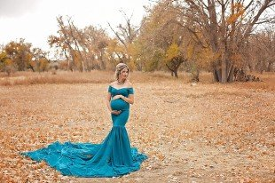 Maternity photo of mother to be in teal gown, standing in a field of fallen leaves.