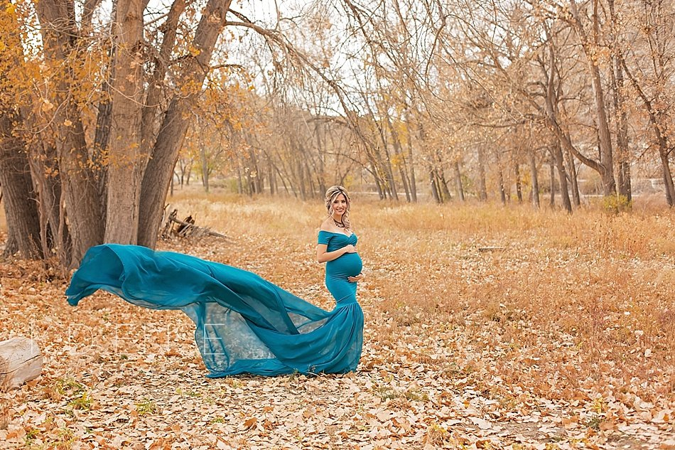 Expecting mother in a teal gown stands in a leaf covered field. Maternity portraits by Pueblo maternity photographer K.D. Elise Photography.