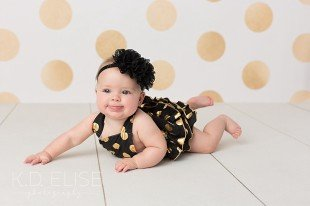 Baby girl in black and gold romper sitting up by Colorado Springs baby photographer K.D. Elise Photography.