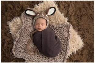 Newborn baby boy laying on brown fur while wearing a deer bonnet. Newborn portraits by K.D. Elise Photography, a Colorado Springs and Pueblo newborn photographer.