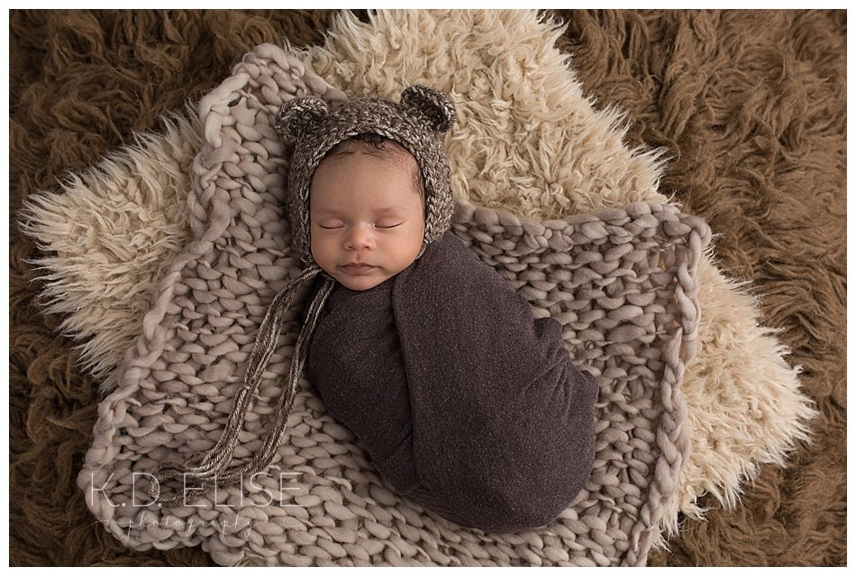 Newborn baby boy in a bear bonnet, laying on brown fur. By Colorado Springs and Pueblo newborn photographer.