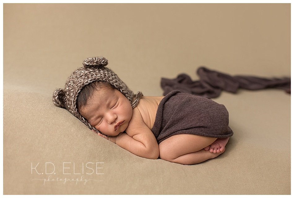 Newborn baby boy in a bear cap, sleeps during his newborn baby photos.