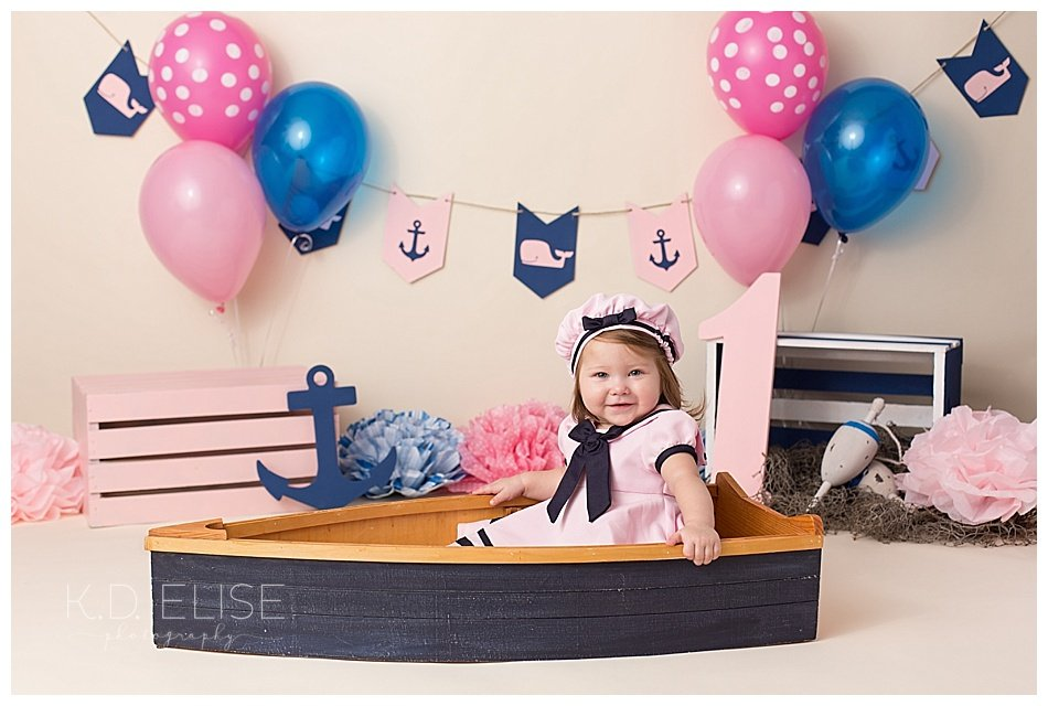 Nautical themed cake smash portrait of baby girl sitting in a blue boat.