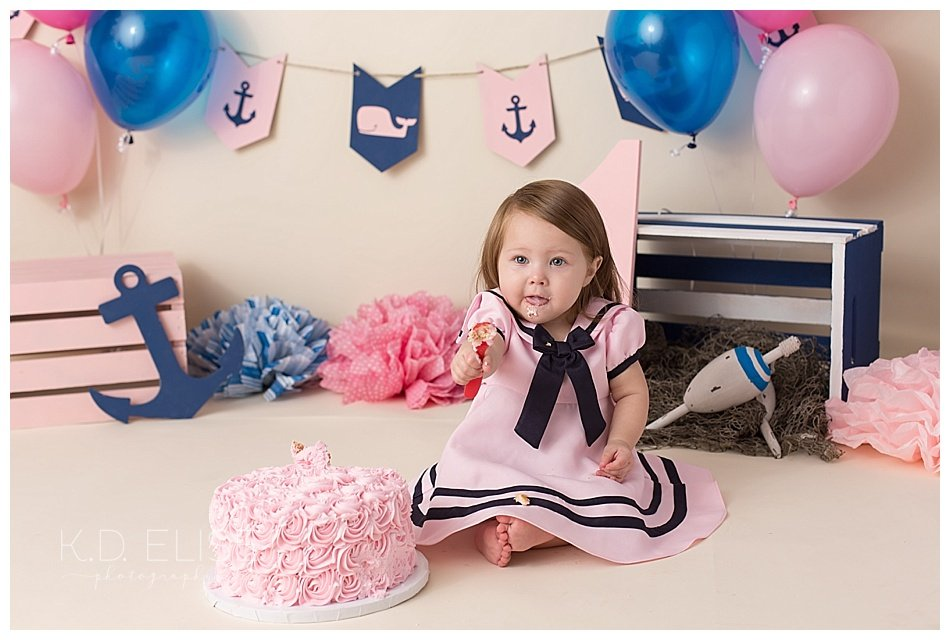 Baby girl eating birthday cake during nautical themed cake smash session with Pueblo photographer K.D. Elise Photography.