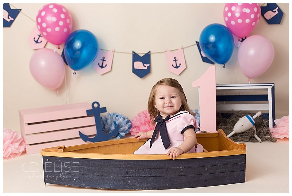 First birthday portrait of baby girl sitting in a blue boat prop. Nautical themed cake smash by Colorado Springs baby photographer K.D. Elise Photography.