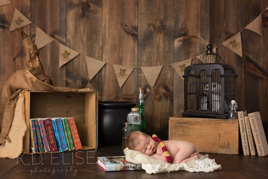 Harry Potter themed newborn photo of baby boy lying on a Harry Potter book while surrounded by Harry Potter themed props.