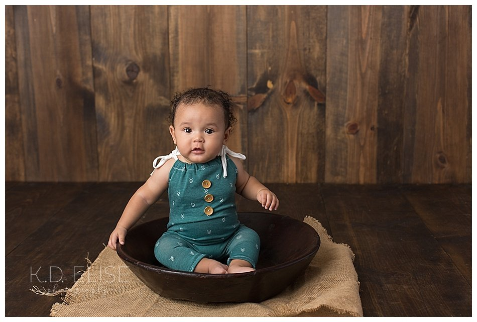 Six month baby photos of little boy sitting in a wooden bowl.