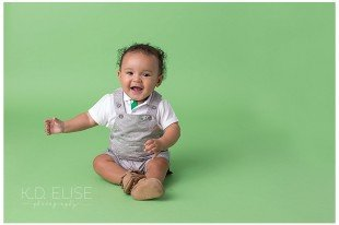 Smiling six month baby boy in grey overalls on a green backdrop.