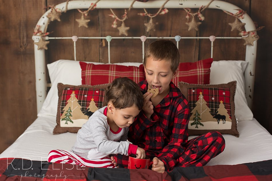 Christmas mini session photo of two kids in a rustic bed, eating milk and cookies.