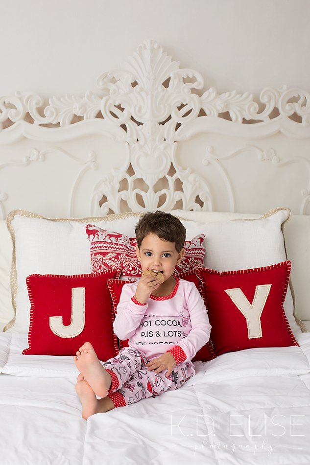 Christmas mini session photo of little girl in pink pajamas sitting on a white and red bed.