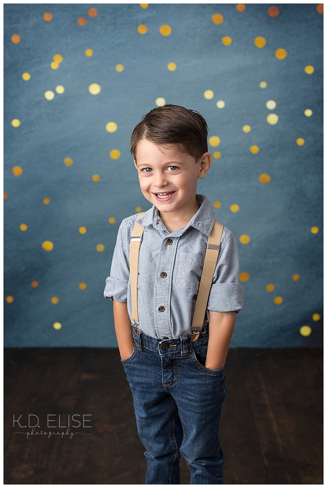 Smiling little boy in blue shirt and blue jeans in front of a blue backdrop.