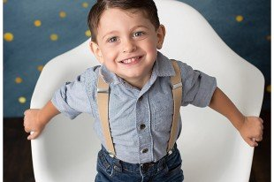 Smiling little boy looks at the camera during his three year birthday portraits.