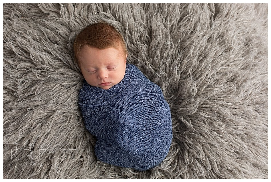Newborn baby boy wrapped in blue laying on a grey fur.