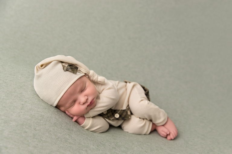 Newborn baby boy in sleepy cap and sleeper laying on his side. Photo by Pueblo Colorado Springs newborn photographer K.D. Elise Photography.