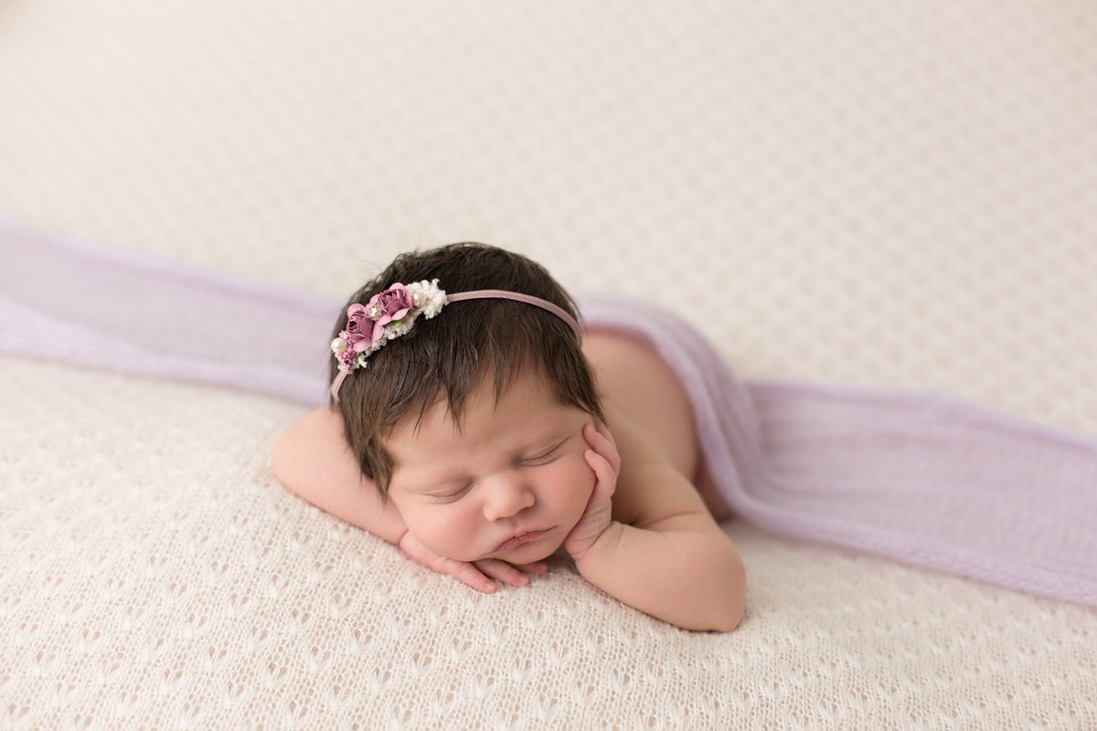 Sleeping baby girl in purple on a cream backdrop by Pueblo Colorado Springs newborn photographer K.D. Elise Photography.