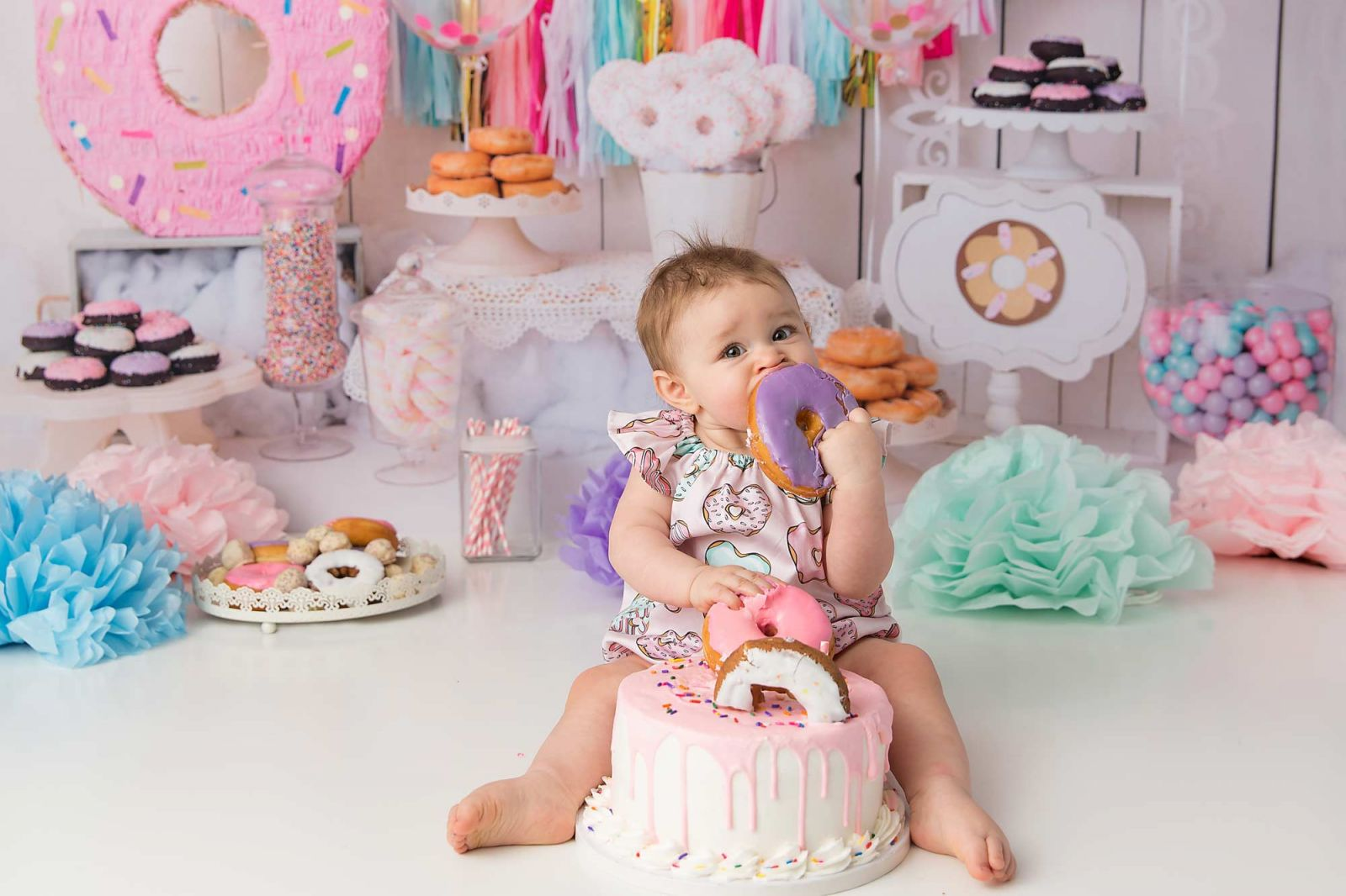 Baby girl eating a donut during donut themed cake smash by Pueblo photographer K.D. Elise Photography.