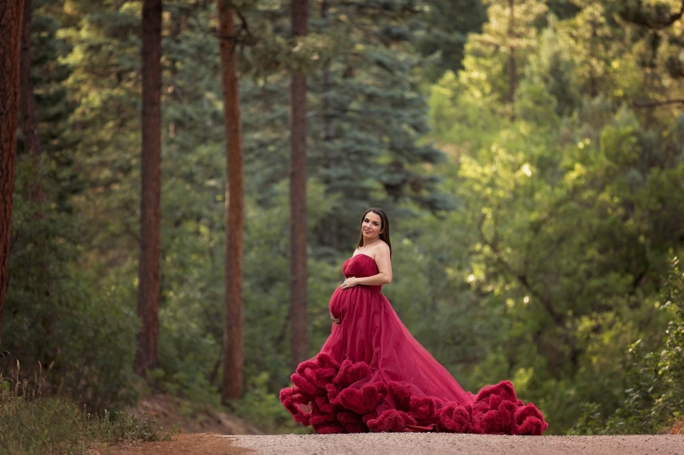 Pregnant woman in red gown stands in the middle of the forest. Portrait by Pueblo Colorado Springs maternity photographer K.D. Elise Photography.