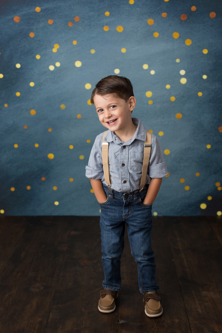 Smiling four year old boy in front of a blue and gold backdrop by Pueblo Colorado Springs children's photographer K.D. Elise Photography.