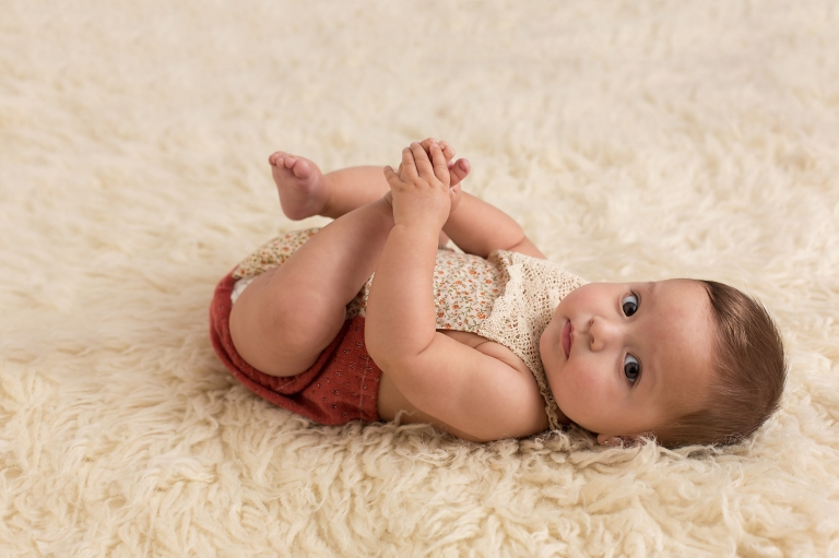 Six month old baby girl in vintage romper laying on the floor and looking at the camera. Photo by Pueblo Colorado Springs baby photographer K.D. Elise Photography.